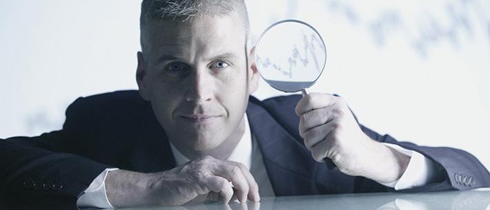 Geschäftsmann mit Lupe analysiert das Unternehmen